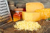 picture of grating  - Grated cheese on wooden cutting board - JPG