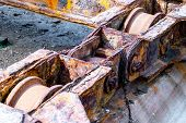 pic of machinery  - Detail of rusted wheels machinery of a old shipyard ramp disused - JPG