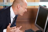 foto of frown  - Businessman frowning in front of computer monitor - JPG