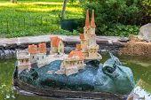 stock photo of garden snail  - garden statue of a snail with castle on its back in a pond - JPG