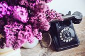 image of rotary dial telephone  - Home interior decor, bouquet of lilacs in a vase, a vintage rotary phone and books on rustic wooden table, on a white wall background ** Note: Soft Focus at 100%, best at smaller sizes - JPG