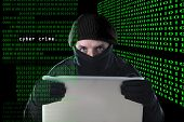 foto of computer hacker  - hacker man in black using computer laptop for criminal activity hacking password and private information cracking password too access bank account data in cyber crime concept - JPG