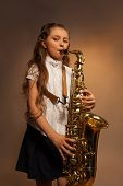 stock photo of gels  - View of girl with long hair playing alto saxophone on the gel colored background - JPG