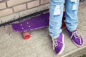 stock photo of snickers  - Teenager in blue jeans and gumshoes stands with skateboard near gray urban wall feet fragment - JPG