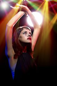 pic of debauchery  - intoxicated female dancing at a nightclub and high on drugs or drunk - JPG