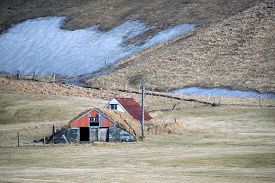picture of iceland farm  - vintage traditional Icelandic farm houses in a valley surrounded by snow covered hills on the southern coast of Iceland during winter - JPG