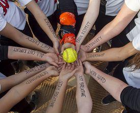 stock photo of fastpitch  - A girls fastpitch softball team inspirational huddle - JPG