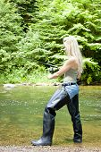 foto of fisherwomen  - young woman fishing in river at summer day - JPG