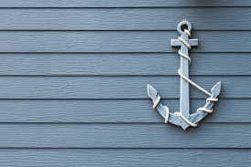 stock photo of anchor  - blue wooden anchor on blue wall background - JPG