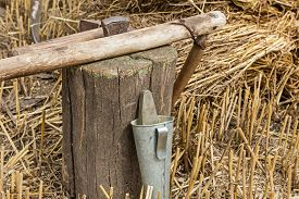 picture of scythe  - Hammer and iron tool for sharpening scythe on the tree stump - JPG