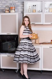picture of ordinary woman  - Happy ordinary woman with pan at her kitchen - JPG