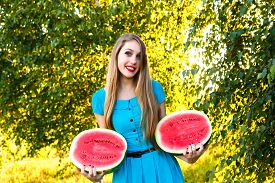 stock photo of cucurbitaceous  - Beautiful young woman holding two halfs of juicy watermelon - JPG