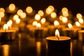 Постер, плакат: Christmas candles burning at night Abstract candles background Golden light of cand