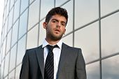 Young Businessman Looking To Camera On Modern Building Background