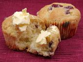 Two Orange Cranberry Muffins With Butter.