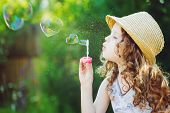 Little Girl Blowing Soap Bubbles In A Heart Shape. Happy Childhood Concept. poster
