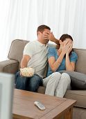 Lovely Couple Hiding Their Face From A Horror Movie Sitting In The Living-room