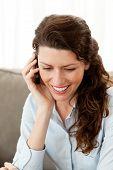 Empresária sorridente ao telefone enquanto descansava no sofá