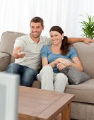Happy Man Changing Channel While Watching Television With His Wife