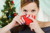 The Young Beautiful Woman Sits Near A Christmas Fur-tree With A Red Cup