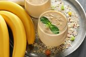 Glass of tasty banana smoothie on table poster