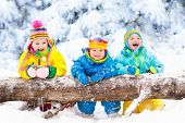 Kids Playing In Snow. Children Play Outdoors In Winter Snowfall. poster