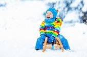 Boy On Sleigh Ride. Child Sledding. Kid With Sledge poster