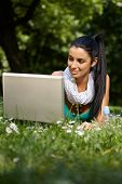 Attractive young girl laying in grass in citypark, using laptop, smiling.?