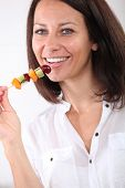 40 years old woman eating a fruits brochette