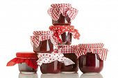 Stack of jam jars with red and white patterned cloth on tops poster