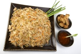 foto of pancit  - Pancit on a ceramic dish with egg rolls and sweet and sour sauce - JPG