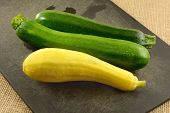 Freshly Rinsed Raw Whole Zucchini And Summer Squash On Black Cutting Board poster