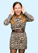 Beautiful middle age woman wearing leopard animal print dress Trying to hear both hands on ear gestu poster