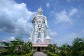 Huge mighty Hanuman statue against cloudy skies in India