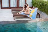 Beautiful Sexy Smiling Girl With Long Hair In A Bikini Sitting On A Lounger Covered With Blue Pareo  poster