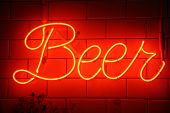 Neon Beer Sign. Orange or Red Neon BEER Sign on a white tile wall. Beer Sign. Neon Sign.  poster