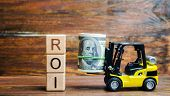 Wooden Blocks With The Word Roi And Money With Forklift. Ratio Between The Net Profit And Cost Of In poster