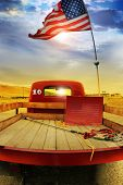 Concept photo of a vintage red vintage pick up truck with American flag waving above against rural d