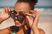 Front view of beautiful happy African american woman looking over sunglasses on beach in the sunshin poster