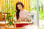 Beautiful Woman Eating Alone In A Summer Cafe. poster