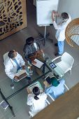 High angle view of Caucasian male doctor explaining graph flip chart in meeting with diverse medical poster