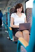 Happy Young Businesswoman Using A Netbook On The Train / Bus