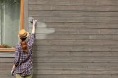 Woman Worker Painting Wooden House Exterior Wall With Paintbrush And Wood Protective Color poster