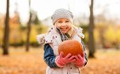 childhood, thanksgiving day and halloween concept - happy little girl with pumpkin at autumn park poster