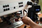 Barista Inserting Portafilter Into Coffee Machine Indoors, Closeup poster