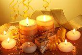 Hermosas velas, regalos y decoración en la mesa de madera sobre fondo amarillo