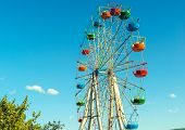 Scenic View Of Beautiful Ferris Wheel In Amusement Park. Large Colorful Ferris Wheel On The Blue Sky poster