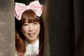 stock photo of lolita  - japanese woman in sweet lolita cosplay  hiding in forest - JPG