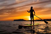 Stand Up Paddle Boarding On A Quiet Sea With Warm Summer Sunset Colors. poster