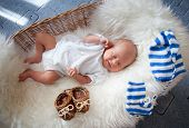 Sleeping newborn baby in wicker basket lying on sheepskin